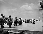 Despite enemy fire, Marines wade through the surf off Tarawa Island. Landing boats and barges brought them to within 500 yards of the beach but the coral bottom prevented the boats from coming any closer to the shore.