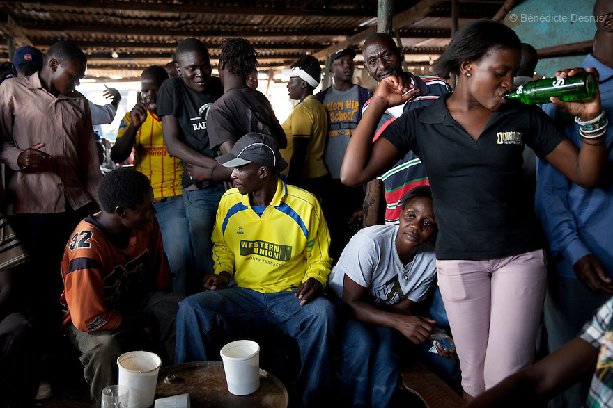 People dance and drink Busaa, a traditional fermented beer, at Madiaba Busaa club at midday in a Nairobi slum on April 21, 2013. Busaa is made by crudely fermenting maize, millet, sorghum or molasses. At Kshs 35 per liter it is much cheaper than a Kshs120 half-liter bottle of commercial beer. The local brew was legalised in 2010 and since then Busaa clubs have become increasingly popular in slums and rural areas. Drinking is on the rise in Kenya, especially among young people. Photo by Benedicte Desrus