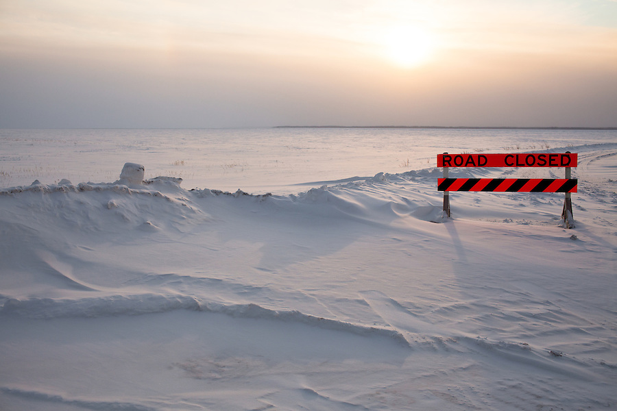 The sun hangs low on the horizon on a cold winter day not far from Enterprise in Northwest Territories as a sign warns travelers not to proceed across the unmarked frozen lake.