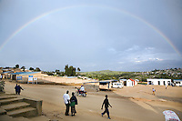 Rwanda. Southern province. Gitarama. District of Muhanga. A full rainbow in the stormy sky. A motorcycle on the concrete road. People walk on the sidewalk. A couple, man and woman, stands  close together. © 2007 Didier Ruef