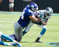 The Carolina Panthers played the New York Giants at Bank of America Stadium in Charlotte, NC.  The Panthers won 38-0 for their first victory of the season.  The Giants dropped to 0-3.  New York Giants center David Baas (64) tackles Carolina Panthers cornerback Melvin White (23).