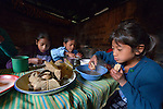 Children eat breakfast at their home in Tuixcajchis, a small Mam-speaking Maya village in Comitancillo, Guatemala. They are, from left, Lidia, 11; Elder, 6; and Vilma Diaz Vasquez, 9.