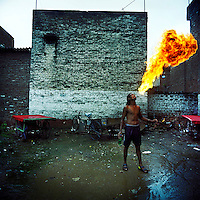 Rahul the Fire Eater practices his art in the Kathputli Colony. Located in northwest Delhi, Kathputli is inhabited by approximately 2,000 performing artists, practicing traditional art forms such as marionette puppetry, juggling, magic, acrobatics, dance and music. Many have travelled all over the world showcasing their abilities, but they still choose to remain living in this slum, which is one of the most impoverished in the city.