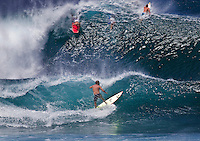 Surfers and bodyboarders in fast-paced action at Banzai Pipeline on North Shore of Oahu.