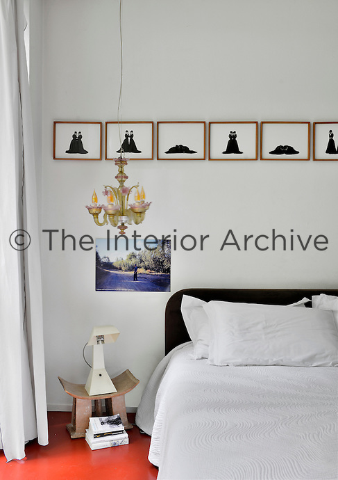 A White bedroom with an orange red floor. A collection of black and white artworks are displayed in a row above a bed. A contemporary lamp stands on a small bedside table.