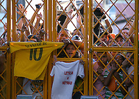 Brazil supporters pile in behind a set of gates as they try to get a peek of their side during training ahead of tomorrow's World Cup quarter final vs Colombia