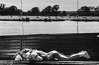A girl sleeps aboard a small ship on the River Thames.