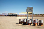 Litter barrels with moving RV in the background on the highway between Quartzite and Yuma, Arizona, USA.