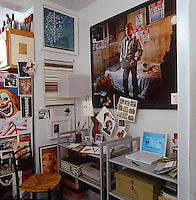 A corner of the kitchen serves as a home office and the walls are covered with posters, cards and memorabilia