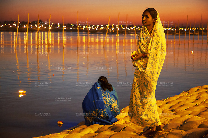 India. Uttar Pradesh state. Allahabad. Maha Kumbh Mela. Two Indian Hindu devotees in Sangam at night. Both women wear sarees. The Kumbh Mela, believed to be the largest religious gathering is held every 12 years on the banks of the 'Sangam'- the confluence of the holy rivers Ganga, Yamuna and the mythical Saraswati. In 2013, it is estimated that nearly 80 million devotees took a bath in the water of the holy river Ganges. The belief is that bathing and taking a holy dip will wash and free one from all the past sins, get salvation and paves the way for Moksha (meaning liberation from the cycle of Life, Death and Rebirth). Bathing in the holy waters of Ganga is believed to be most auspicious at the time of Kumbh Mela, because the water is charged with positive healing effects and enhanced with electromagnetic radiations of the Sun, Moon and Jupiter. The Maha (great) Kumbh Mela, which comes after 12 Purna Kumbh Mela, or 144 years, is always held at Allahabad. Uttar Pradesh (abbreviated U.P.) is a state located in northern India. 7.02.13 © 2013 Didier Ruef