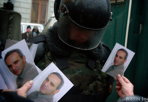 A woman carrying pictures of former world chess champion Garry Kasparov demonstrates in Moscow against what she said were rigged presidential elections..Russia went to the poll the day before to vote for Vladimir Putin's chosen successor, Dmitry Medvedev. .The protesters are part of a loose coalition of opposition members led by Kasparov and writer Eduard Limonov.
