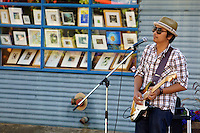 Young blues guitarist and singer performing outdoors, Granville Island,  Vancouver, British Columbia, Canada