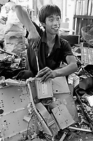 China. Province of Guangdong. The village of Nanyang is part of the town of Guiyu. A worker with a cigarette in his mouth and a screwdriver in his right hand takes down an old computer and its electronic components which will then be laid on the ground. The various parts will be recycled for its metals, electric cables, terminals, printed and integrated circuits, chips,... © 2004 Didier Ruef