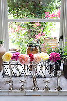 Individual rose heads in tiny glass vases decorate the kitchen window sill