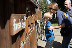 Tommy Morphord and his mom take a glimpse inside a henhouse at the Hartley Coop and Farm Stand in Los Altos Hills.