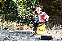 A kid playing accordion in the street of Athens, Greece
