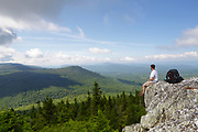 A hiker enjoys the view from the summit of Black Mountain in Benton, New Hampshire during the summer months.