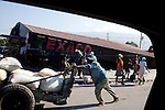A man pushes a cart past a Texaco station in Port-au-Prince, Haiti, that collapsed in the recent earthquake.