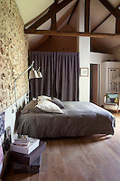 The master bedroom is situated under the rafters on the attic floor where the rough stone walls have been left exposed