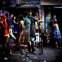 The Tall-Man waits for an audience in the Kathputli Colony before strapping on his Stilts. Located in northwest Delhi, Kathputli is inhabited by approximately 2,000 performing artists, practicing traditional art forms such as marionette puppetry, juggling, magic, acrobatics, dance and music. Many have travelled all over the world showcasing their abilities, but they still choose to remain living in this slum, which is one of the most impoverished in the city.