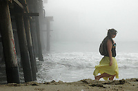 A woman walks past the Santa Monica Pier.