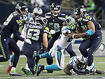 Seattle Seahawks running back Thomas Rawls (34) breaks the tackles of Carolina Panthers free safety Michael Griffin (22) and Carolina Panthers defensive tackle Kyle Love (77) on his way to a 13-yard gain in the third quarter at CenturyLink Field in Seattle, Washington on December 4, 2016.  Rawls ran for 105 yards on 16 carries and scored two touchdowns in the Seahawks 40-7 win over the Panthers.  ©2016. Jim Bryant photo. All Rights Reserved.