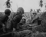 Marines taking part in the assault on Namur Island gather together in the shelter of a seawall to formulate plans for the advance on Japanese positions.