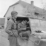 April 1945.Lt. Richard Hoorn standing next to jeep while Pvt. Ray Fisher types as he sits inside the jeep. Austria