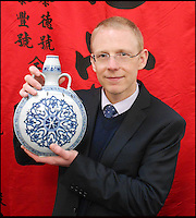 BNPS.co.uk (01202 558833).Pic: Dukes/BNPS..Over the moon...flask...Auctioneer Andrew Marlborough with the £120,000 vase...A broken Chinese vase that was delivered by its elderly owner to an auction house in a battered cardboard box has sold for £120,000...The man, aged in his 80s, had inherited the 11 inch moonflask vase from a relative many years ago and had no idea of its worth...The top part had once broken off and had been very crudely stitched back together using large metal staples, a technique last used by ceramic specialists in the 1960s...Although experts suspected the piece dated back to Imperiel China, the ugly 11ins-long scar led to them to put a 2,000 pounds pre-sale estimate on it...But scores of Chinese collectors lined up to bid on the blue and white vase when it came up for auction, reaffirming the belief the piece dated back to the 15th century...It was finally bought for 119,500 pounds. Had it not had the hefty crack running through it, it is likely the Ming vase would have fetched one million pounds..