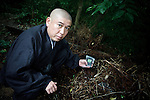Fukushima city, August 2nd 2011 - Priest Koyu Abe showing a dosimeter on a highly radioactive location (15microsv/h) , next to his temple.