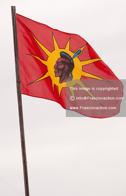"""A Mohawk Warriors Society flag flies on a property in the Huron reserve of Wendake near Quebec city January 4, 2010. Designed to serve as a symbol and standard for the """"vanguard of the Long House people"""" the Flag of the Mohawk Warrior Society was designed by the late Mohawk artist and scribe Karoniaktajeh."""
