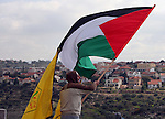 A Palestinian demonstrator holds a Palestinian flag during a protest against Israel's controversial separation barrier in the West Bank village of Nilin, near the city of Ramallah, Friday, Jan. 1, 2010. Photo by Issam Rimawi