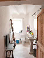 The all white bathroom is a mixture of contemporary and rustic furniture and fittings