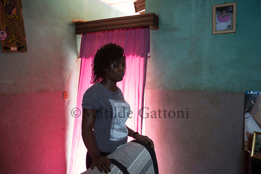 """Cameroon - Yaoundé - Emilia Ngabi, 21, stands in her uncle's living room where she has been living since both her parents passed away. In January 2015, Leonge, her 35 years olf brother left for Europe. """"I implored him to come back so many times, but he said he couldn't. He was determined to go"""". In May 2016, Leonge called her sister one last time from Libya, telling her he would try to cross in the following days and that he would call back once he had reached Italy. That was the last time Ngabi heard his voice. Then, on the 24th of May, at 11.30pm, Ngabi saw a friend posting a message on his brother's Facebook page. It read """"rest in peace."""""""