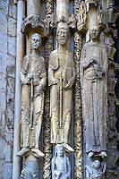.West Facade, Left Portal c. 1145,  Cathedral of Notre Dame, Chartres, France. Gothic statues of three elongated jamb statues are on the left side of the left portal. All have canopies and stand on figural bases. All hold books or scrolls. Their height increases from left to right. Note the figured columns between them.. A UNESCO World Heritage Site. .