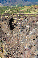 An old rock wall backed by mountains in Kaupo, Maui.