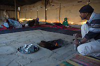 Bedouin man grinds coffee for his guests in a bedouin tent.  Photo by Oren Nahshon