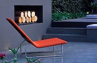 Detail of an orange sun-lounger on a patio beside an outdoor fireplace