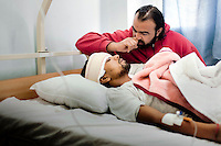 A friend of Salem Fathallah sits at his bedside. He was shot in the head by pro-Gadaffi forces during the fight for Agdabia and is now being treated in the Albatnan hospital. He is still conscious, but in critical condition. The hospital is the principle centre for the treatment of wounded civilians and rebel fighters. On 17 February 2011 Libya saw the beginnings of a revolution against the 41 year regime of Col Muammar Gaddafi.