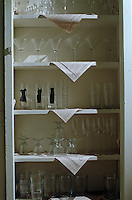 A simple painted cupboard in a kitchen displays a collection of glassware