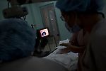 Vietnamese doctors watch a TV screen as Dr. James Brandt performs surgery on a one-month-old child suffering from sever glaucoma in both eyes at the Ho Chi Minh City Eye Hospital on Thursday, April 17, 2008...ORBIS Flying Eye Hospital brought doctors, nurses and specialists from all over the world to Ho Chi Minh City, Vietnam from April 7-18, 2008.  The ORBIS program contributed to the efforts of Ho Chi Minh City Eye Hospital in fighting avoidable blindness by educating local ophthalmologists to diagnose and manage pediatric blindness, retinal disease, oculoplastics, and blindness due to glaucoma.
