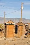 Three wooden outhouses, power pole and lines, Nevada