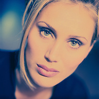 Tight, cross processed photo of the face of a beutiful blond woman.