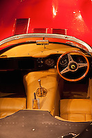 A view from above into the driver's cockpit of a right-hand drive Jaguar E-Type convertible sports car.