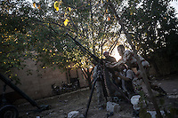In this Tuesday, Oct. 08, 2013 photo, opposition fighters fix up a machine gun as a helicopter flies overhead at the frontline in Maraat Al-Nouman in the Idlib province countryside of Syria. (AP/Photo)