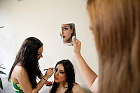 Female models apply their make-up prior to a photo shoot.