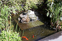 In the garden a Matisse-inspired fishpond is surrounded by lush planting whilst water cascades from the central stone sculpture