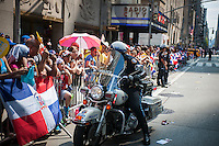 NYPD motorcycle officer with spectators in the Dominican Day Parade in New York on Sixth Avenue on Sunday, August 11, 2013.  Politicians, flags and cultural pride were on display at the annual event.  (© Richard B. Levine)