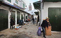 Shopkeepers closing up in a narrow street in the medina or old town, with a minaret in the distance, Tetouan, on the slopes of Jbel Dersa in the Rif Mountains of Northern Morocco. Tetouan was of particular importance in the Islamic period from the 8th century, when it served as the main point of contact between Morocco and Andalusia. After the Reconquest, the town was rebuilt by Andalusian refugees who had been expelled by the Spanish. The medina of Tetouan dates to the 16th century and was declared a UNESCO World Heritage Site in 1997. Picture by Manuel Cohen