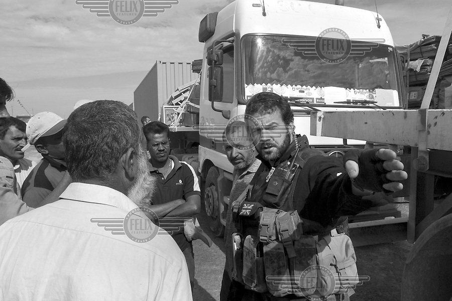 Private security operator Karl Moore from the British company ArmorGroup briefs civilian truck drivers at a convoy staging area near Baghdad, Iraq on October 22, 2006.  The coalition forces and civilian administration in Iraq depend heavily on thousands of controversial security contractors to support their reconstruction efforts and military operations.